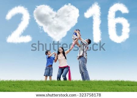 Photo of happy asian family enjoy new year holiday at field with cloud shaped numbers 2016