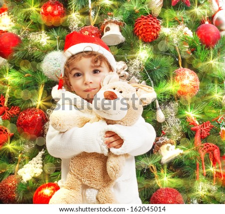 Photo of happy boy holding teddy bear in hands on beautiful decorated Christmas tree background, little child wearing red Santa Claus hat, New Year celebration, winter holiday concept - stock photo