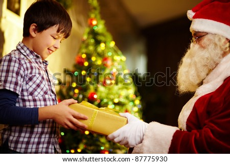 Photo of happy boy taking gift from Santa Claus hands - stock photo