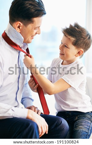 Photo of happy boy tying necktie of his father