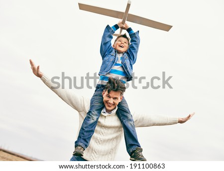 Photo of happy boy with toy airplane and his father against sky