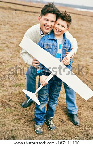 Photo of happy boy with toy airplane and his father looking at camera outdoors - stock photo