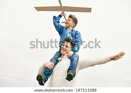 Photo of happy boy with toy airplane and his father playing outside - stock photo