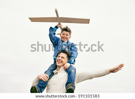 Photo of happy boy with toy airplane and his father playing outside