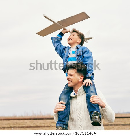 Photo of happy boy with toy airplane and his father playing together outside