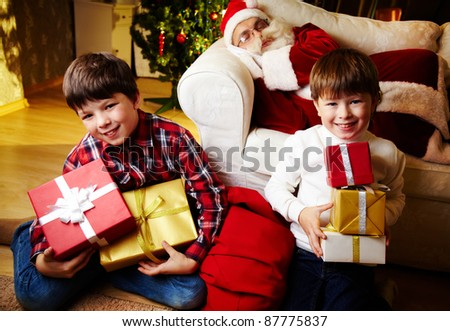 Photo of happy boys looking at camera with Santa Claus sleeping on sofa on background - stock photo