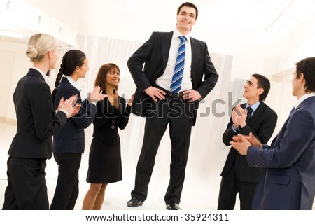 Photo of happy business partners applauding to confident leader surrounded by them