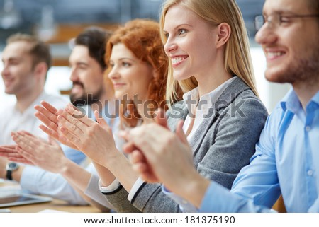 Photo of happy business people applauding at conference, focus on smiling blonde - stock photo