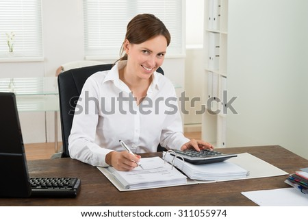 Photo Of Happy Businesswoman Calculating Invoice At Desk - stock photo