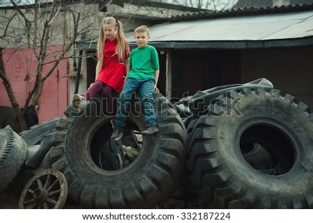 photo of happy children playing in junkyard tires