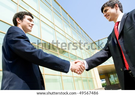 Photo of happy co-workers handshaking outdoors at background of modern building - stock photo