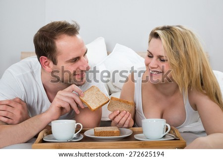 Photo Of Happy Couple Having Breakfast In Bedroom - stock photo