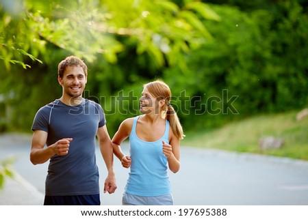 Photo of happy couple jogging on summer morning - stock photo