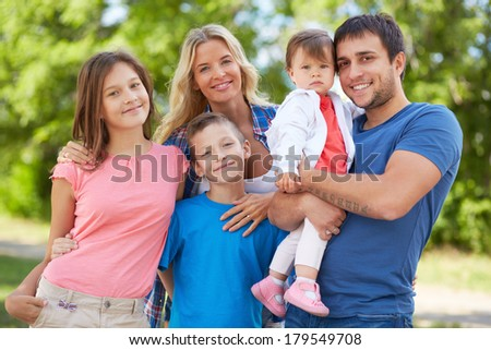 Photo of happy family looking at camera outdoors - stock photo