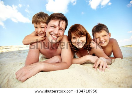 Photo of happy family lying on beach and sunbathing on summer day - stock photo