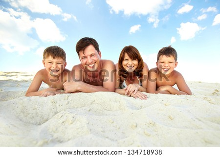 Photo of happy family lying on beach and sunbathing on summer vacation