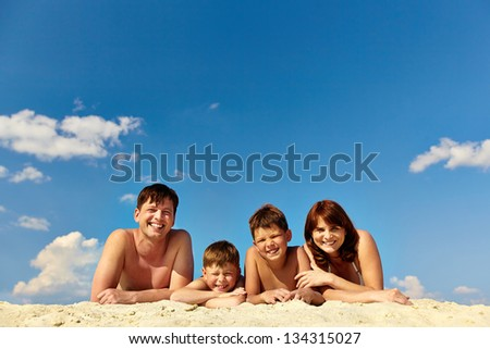 Photo of happy family lying on sand and sunbathing on summer vacation