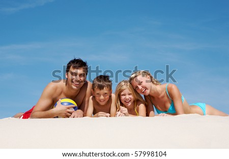 Photo of happy family lying on sand on summer vacation - stock photo