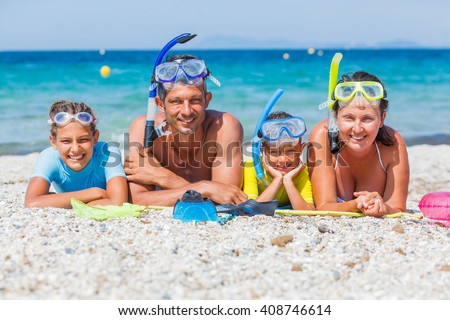 Photo of happy family of divers looking at camera during summer vacation on the tropical white beach - stock photo