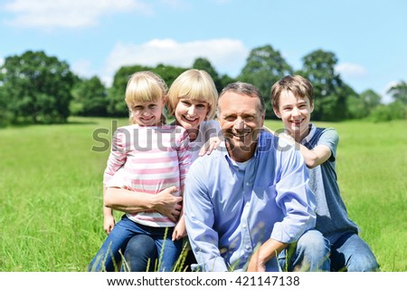 Photo of happy family of four sitting on grass.