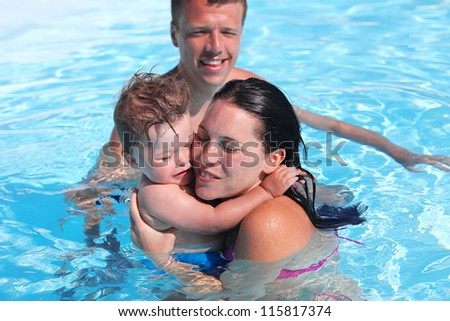 Photo of happy family of parents and cute son in swimming pool - stock photo