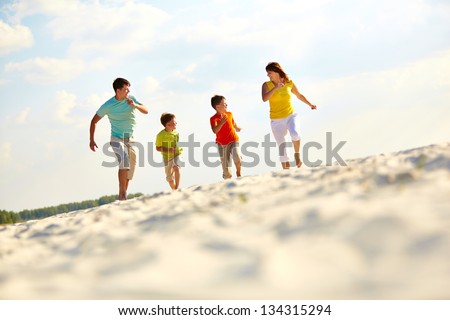 Photo of happy family running down sandy beach on summer