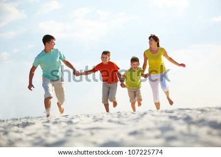 Photo of happy family running down the beach on summer