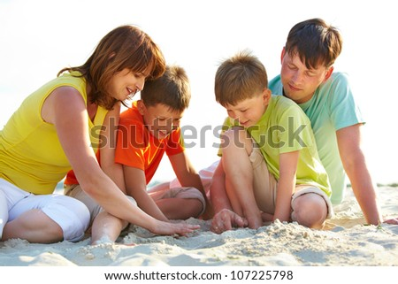 Photo of happy family sitting on sand during summer rest - stock photo