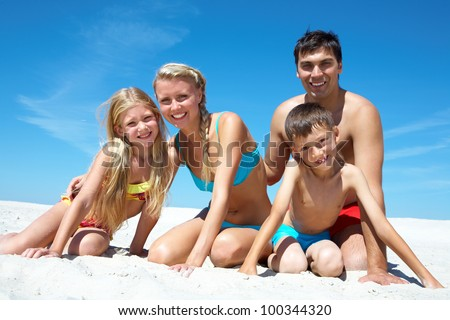 Photo of happy family sitting on sand on summer vacation - stock photo