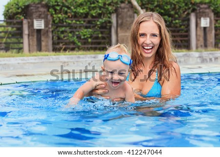 Photo of happy family - swimming and having fun woman and little child in goggles. Focus on baby. Family lifestyle and water sport activity, lessons with parents in swimming pool on summer vacation.