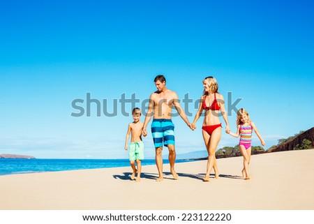 Photo of Happy Family Walking Down the Beach - stock photo