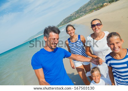 Photo of happy family with three kids running down the beach