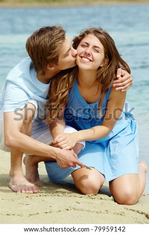 Photo of happy girl being kissed by her boyfriend during summer vacation - stock photo
