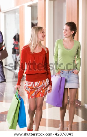 Photo of happy girls walking down trade center and chatting - stock photo