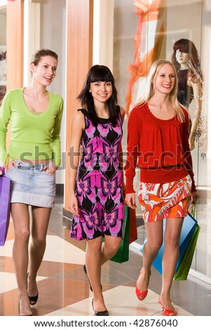 Photo of happy girls walking down trade center during shopping