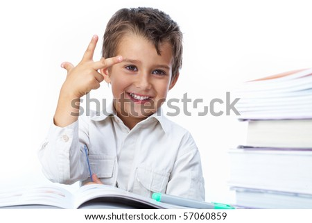 Photo of happy kid sitting at the table with open book before him - stock photo