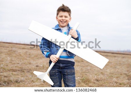 Photo of happy kid with toy airplane looking at camera outside - stock photo