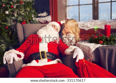 Photo of happy littlle smiling girl looking at sleeping Santa Claus with big bag of presents