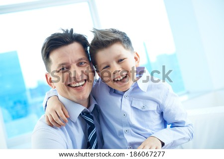 Photo of happy man and his son embracing and looking at camera