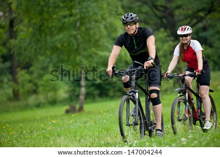 Photo of happy Man and woman exercising with bicycles outdoors, in forest