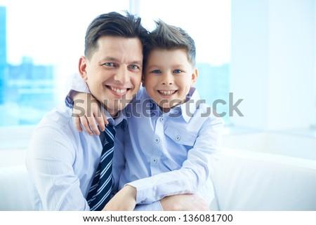 Photo of happy man embracing his son and both looking at camera - stock photo