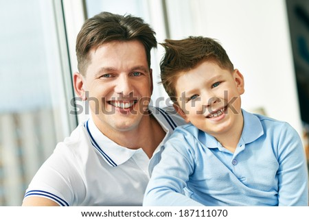 Photo of happy man embracing his son and both looking at camera - stock photo