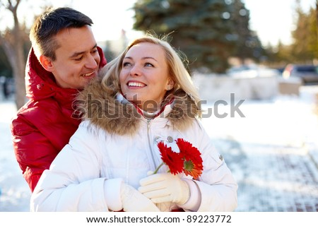 Photo of happy man embracing pretty woman outdoor in winter