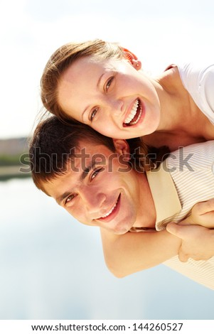 Photo of happy man giving piggyback to his girlfriend and both looking at camera