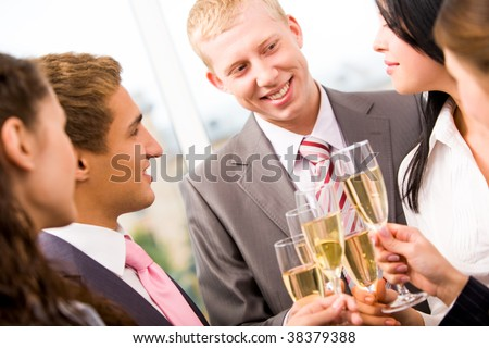 Photo of happy man holding flute with champagne and smiling at colleagues during party