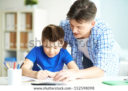 Photo of happy man looking at his son writing in copybook at home - stock photo