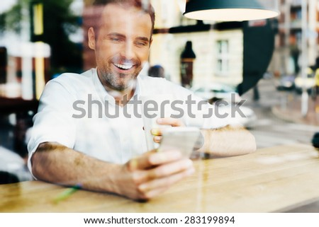 Photo of happy man looking at smartphone in cafe. - stock photo