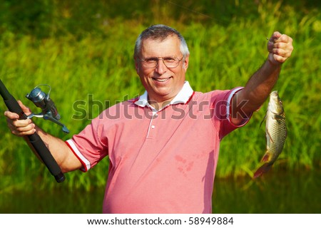 Photo of happy mature man showing carp caught by him