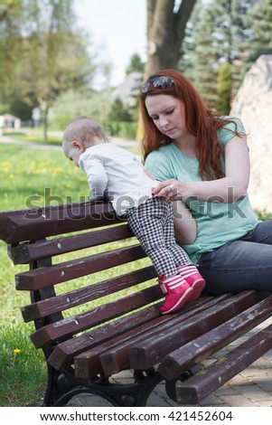 photo of happy mother and child sitting outdoors - stock photo