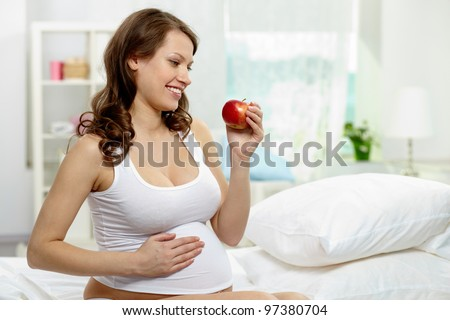 Photo of happy pregnant woman holding ripe apple - stock photo